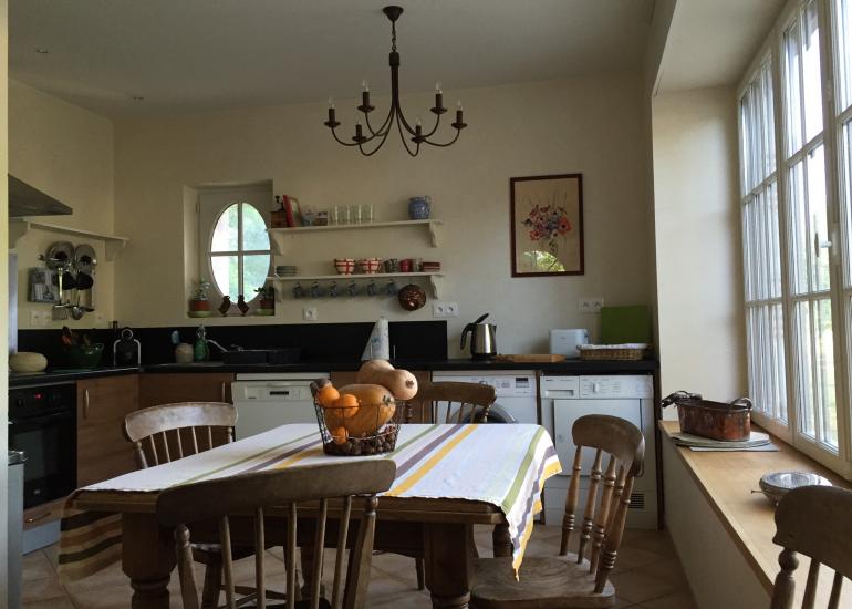 Une cuisine salle à manger baignée de soleil grâce à la baie vitrée.