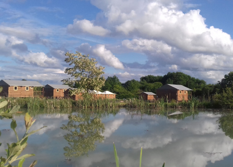 Lodges vus depuis l'étang avec reflets